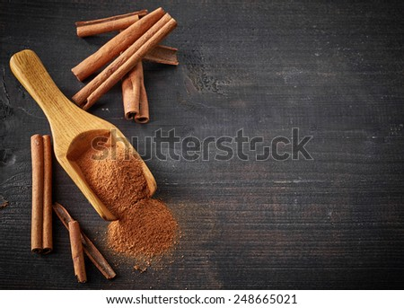 Cinnamon sticks and powder on wooden table - stock photo