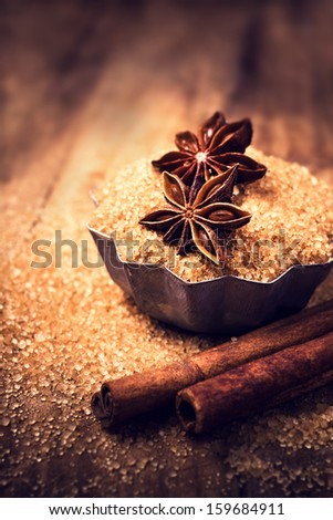 Cinnamon sticks and star anise on brown  sugar on wooden background - stock photo
