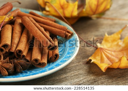 Cinnamon sticks and stars anise with yellow leaves on wooden background - stock photo