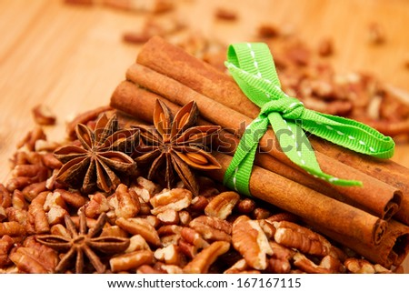 Cinnamon sticks, anise and pecan nuts on kitchen board