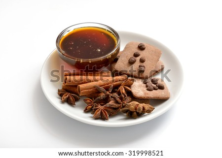 Cinnamon sticks, anise stars and honey on a white plate - stock photo