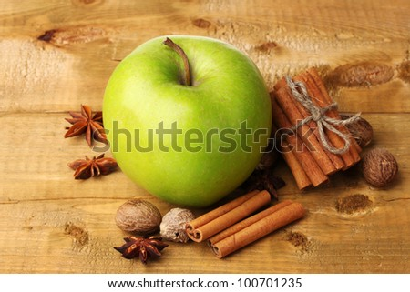 Cinnamon sticks, green apple, nutmeg,and anise on wooden table
