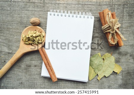 cinnamon sticks,ground cinnamon,Notepad,writing,cooking,Bay leaves on wooden background - stock photo