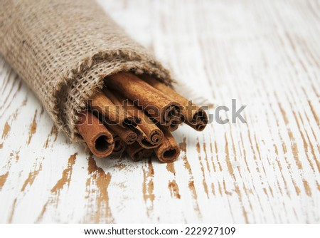 Cinnamon sticks in a burlap sack on the wooden table  - stock photo
