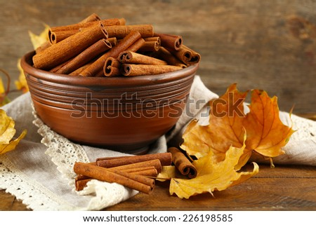 Cinnamon sticks in bowl with yellow leaves on wooden background - stock photo