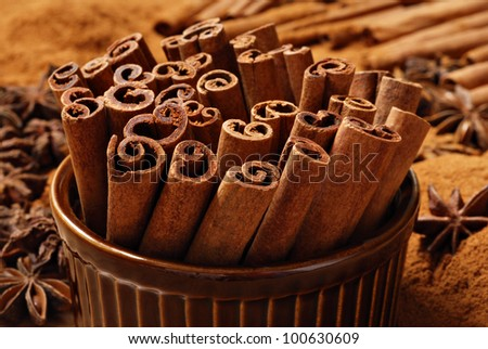 Cinnamon sticks in brown ceramic ramekin with ground cinnamon and star anise in background.  Macro with shallow dof. - stock photo