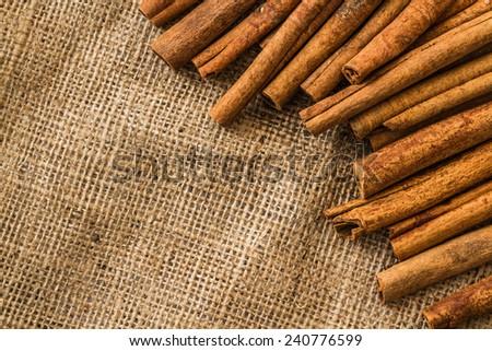 Cinnamon sticks in straw basket on a linen napkin - stock photo
