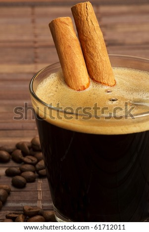 cinnamon sticks inside espresso in a short glass coffee beans aside on wooden background - stock photo