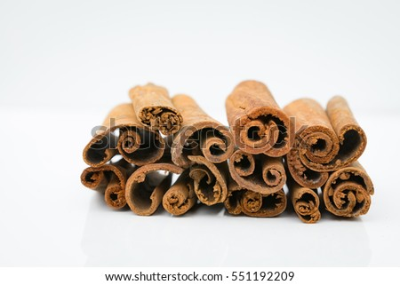 Cinnamon sticks nicely arranged with white background. Cinnamon has a long history as a spice and has a lot of health benefits. Image contain certain grain or noise and soft focus.