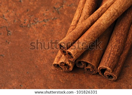 Cinnamon sticks on color coordinated ceramic tile with copy space.  Macro with shallow dof. - stock photo