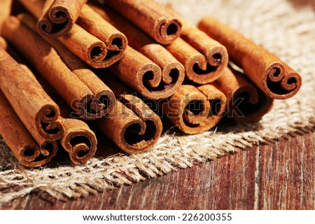 Cinnamon sticks on sackcloth on table close up - stock photo