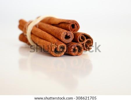 Cinnamon sticks on white reflective background. Selective focus. Macro. - stock photo