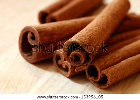 Cinnamon sticks on wood background.  Macro with extremely shallow dof. - stock photo