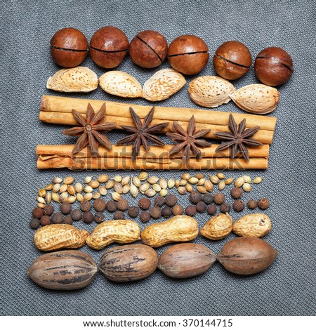 cinnamon sticks, pecans, almonds, macadamia, peanuts, star anise, black allspice, grains of sesame seeds. Beautiful art design of nuts and spices - stock photo