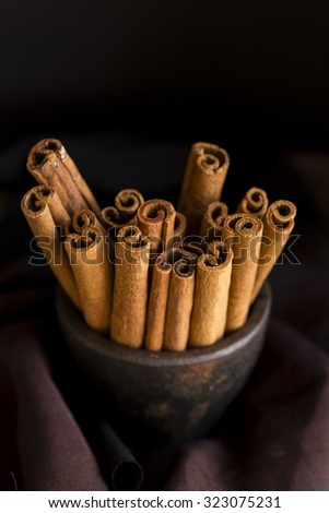 Cinnamon Sticks , Spice Cinnamon Quills are stacked in an iron mortar - stock photo