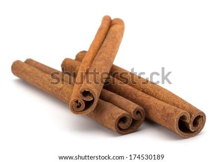 cinnamon sticks stacked on white background - stock photo
