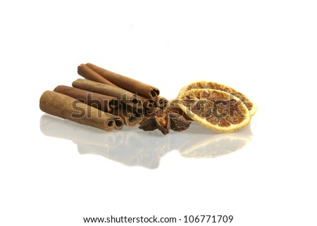 Cinnamon sticks, star anise and dried orange slices on a white background