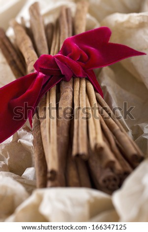 Cinnamon sticks tied with a red ribbon in wrapped paper, Christmas spice for baking background - stock photo