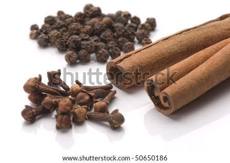 Cinnamon sticks with black pepper seeds and cloves over white background