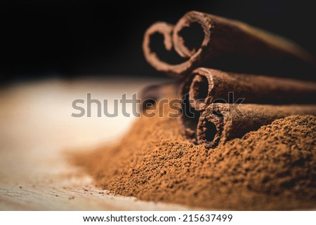 Cinnamon sticks with cinnamon powder on wooden background, Selective focus - stock photo