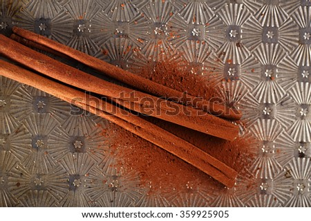 Cinnamon Sticks with Cocoa Powder on old backing metal background - stock photo