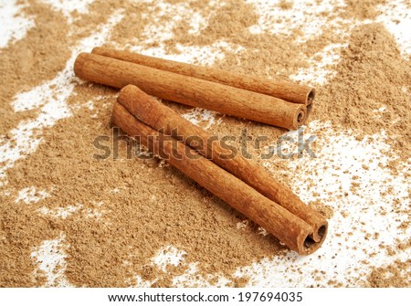 Cinnamon sticks with its dust around it over a white background
