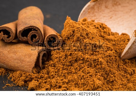 cinnamon sticks with powder on dark stone plate - stock photo