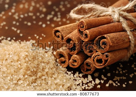 Cinnamon sticks with pure cane brown sugar on wood background.  Macro with extremely shallow dof. - stock photo