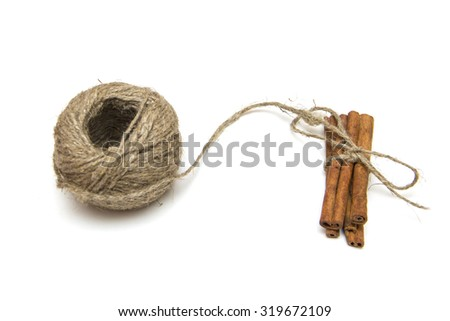 Cinnamon sticks with rope roll isolated on white background