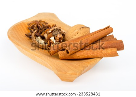 Cinnamon sticks with star anise and crushed nuts on wooden plate and white background - stock photo