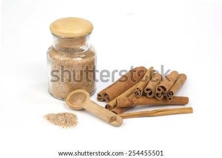 Cinnamon sugar with cinnamon sticks isolated on white - stock photo