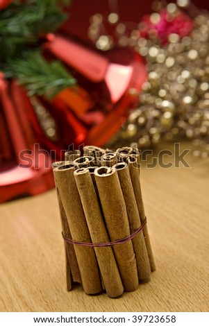 Cinnamon the flavour of christmas with decorations in the background - stock photo