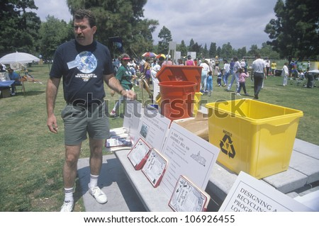 CIRCA 1990 - A coordinator standing by the registration desk ready to hand out instructions on Earth Day - stock photo