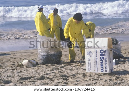 CIRCA 1990 - A man with adsorbent materials to clean up oil washed ashore after a spill near Huntington Beach, California - stock photo