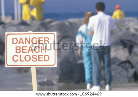 CIRCA 1990 - A sign warning, danger�beach closed with people in the background - stock photo