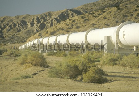 CIRCA 1983 - An aqueduct which supplies water to Los Angeles winding down a hill in the California desert