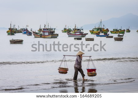 CIRCA APRIL 2010 - QUY NHON, VIETNAM - A woman carries fish baskets by the shore, on 24 April 2010, at Quy Nhon, Vietnam.