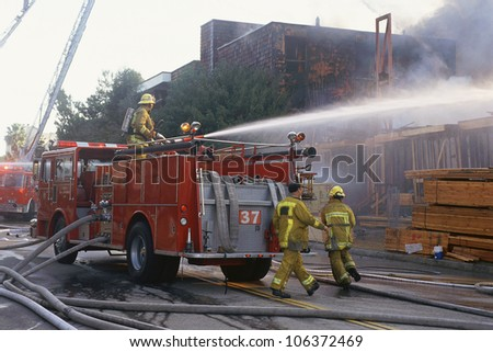 CIRCA 1999 - Firefighters dousing building