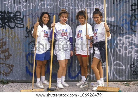 CIRCA 1990 - Four teenage girls participating in community cleanup on Clean and Green Day in East Los Angeles, California - stock photo
