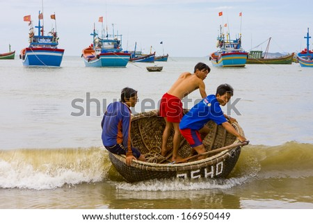 CIRCA JULY 2011 - QUY NHON, VIETNAM - Boys ride a basket boat into the beach, 6 July 2011, in Quy Nhon, Vietnam