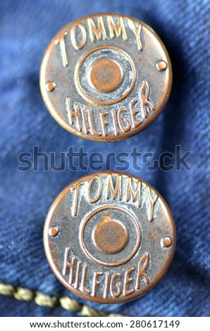 CIRCA JUNE 2014  KWIDZYN: Closeup of Tommy Hilfiger button on blue jeans. Tommy Hilfiger is lifestyle brand founded by American fashion designer Thomas Jacob Hilfiger (born in 1951).