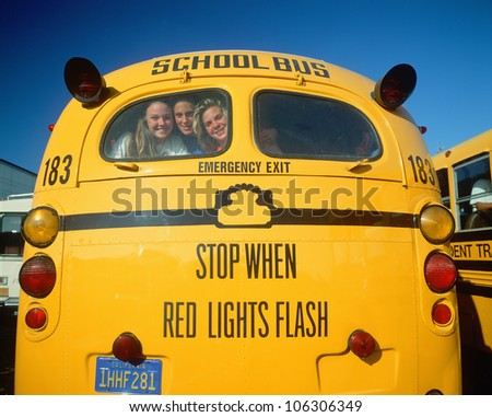 CIRCA 1998 - School girls smiling from back of yellow school bus - stock photo