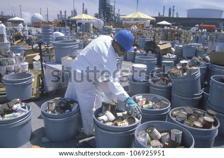 CIRCA 1990 - Worker sorting toxic wastes at waste cleanup site on Earth Day at the Unocal plant in Wilmington, Los Angeles, CA - stock photo