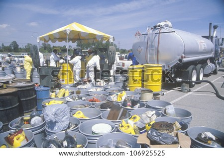 CIRCA 1990 - Workers handling toxic household wastes at waste cleanup site on Earth Day at the Unocal plant in Wilmington, Los Angeles, CA - stock photo
