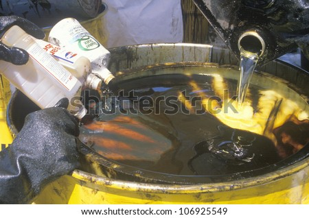 CIRCA 1990 - Workers pouring toxic wastes into a metal drum at waste cleanup site on Earth Day at the Unocal plant in Wilmington, Los Angeles, CA - stock photo