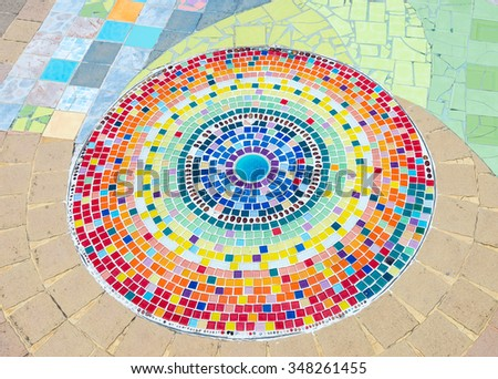 Circle ceramic tile on the floor of theme park. - stock photo