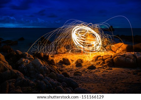 Circle of fire on the beach at twilight time - stock photo