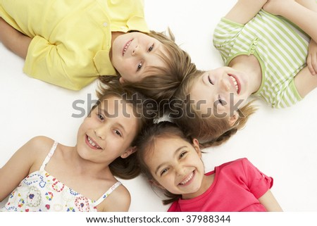 Circle of four young friends lying down smiling - stock photo