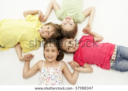 Circle of four young friends smiling and holding hands - stock photo