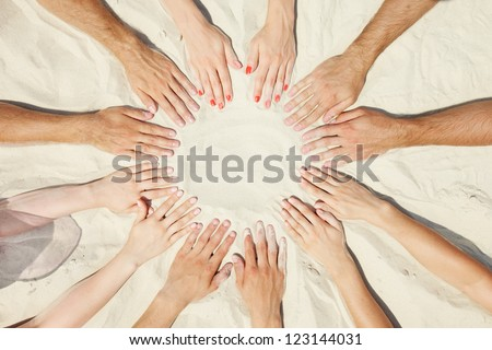 Circle of hands of friends on sand - stock photo